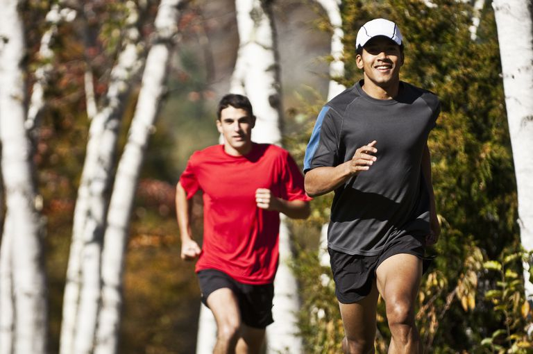 two men running outdoors in forest