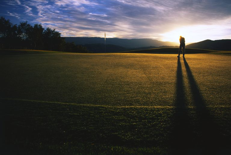 Golfer practicing his putting in silhouette