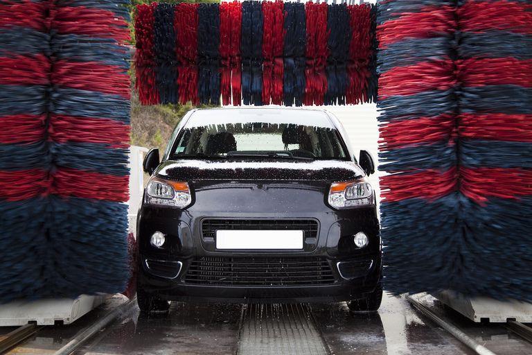 Black car traveling through an automatic car wash