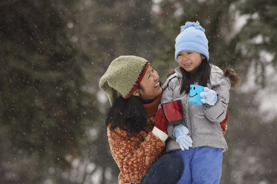 Chinese mother hugging daughter in the snow and drinking hot chocolate