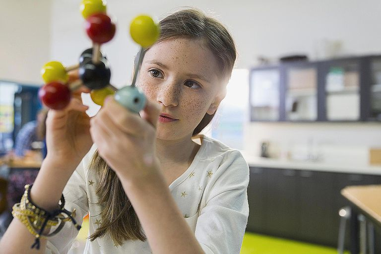A girl studies molecules in a chemistry class room, illustrating the traditional opportunity structure of education as a pathway to success in the U.S.
