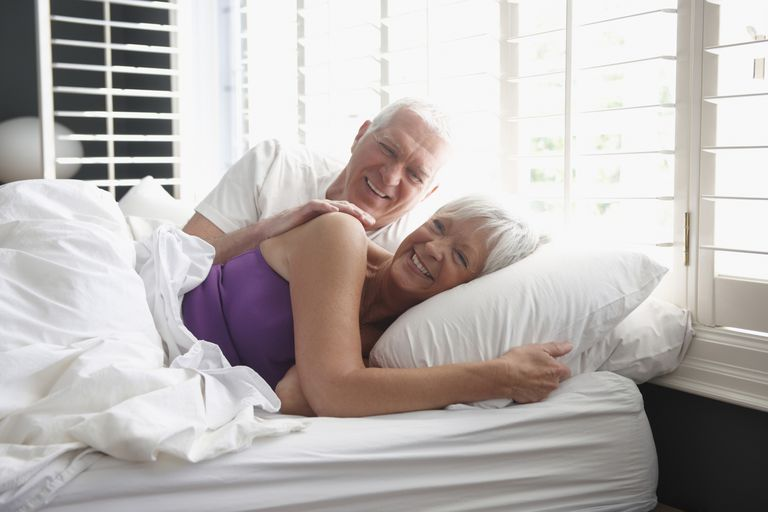 Caucasian couple laying in bed smiling