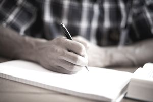 Man writing with a pen on a notepad