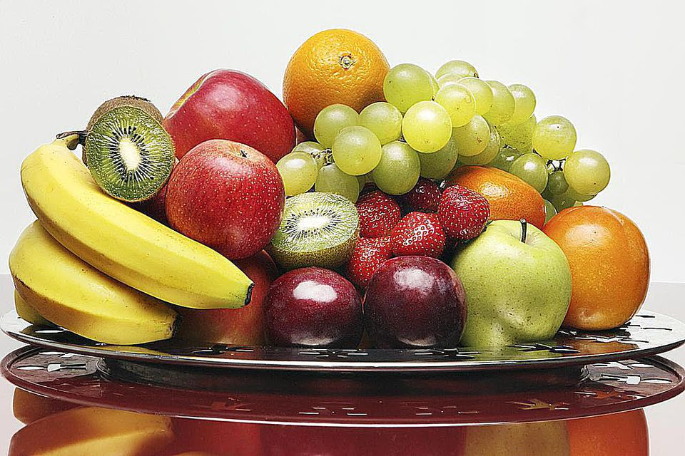 A bowl of fruit sits on a clean background