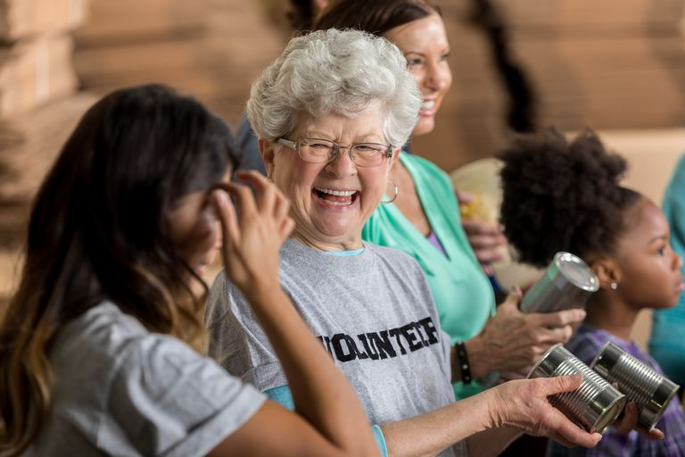 Laughing senior woman wearing a volunteer shirt at a food drive