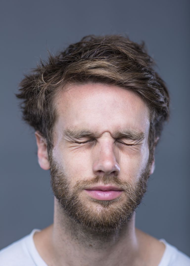 A bearded man with his eyes closed tightly