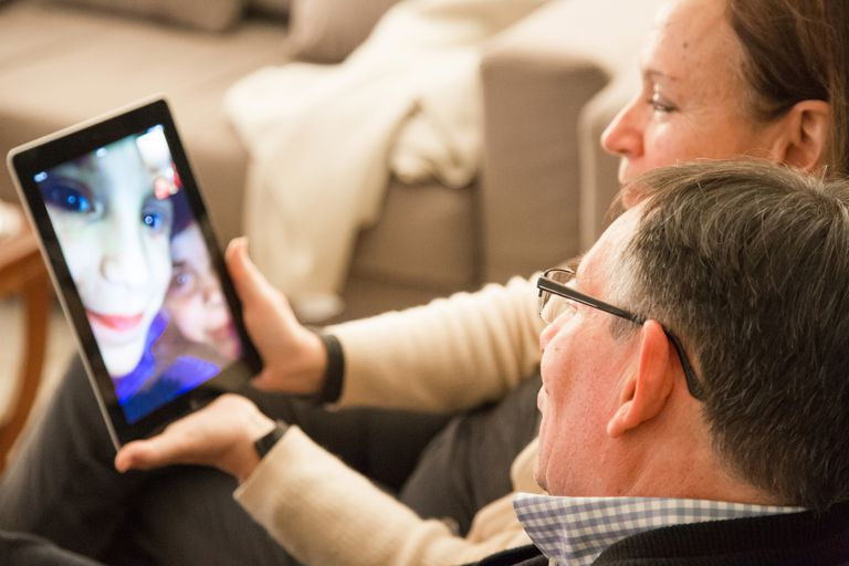 Family with grandparents doing Facetime with iPad.