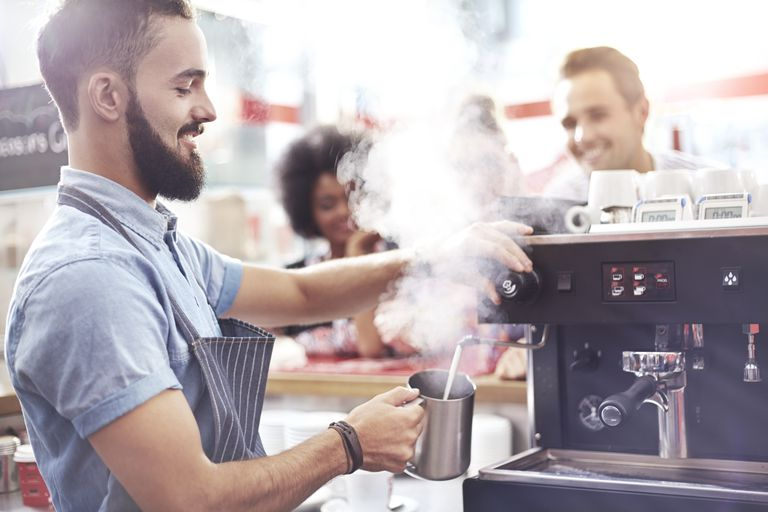 Barista steaming milk in cafe