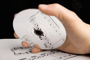 A man holding an audio CD above sheet music