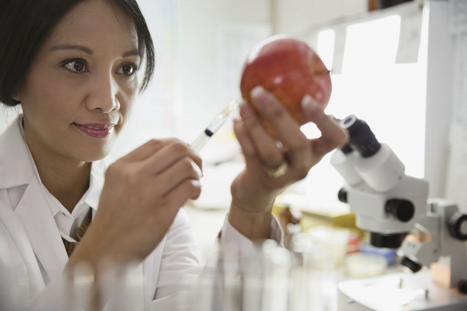 Mature female scientist extracting liquid from apple in laboratory