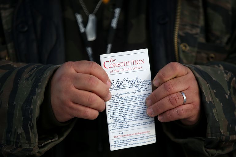 Man holding a study guide to the US Constitution