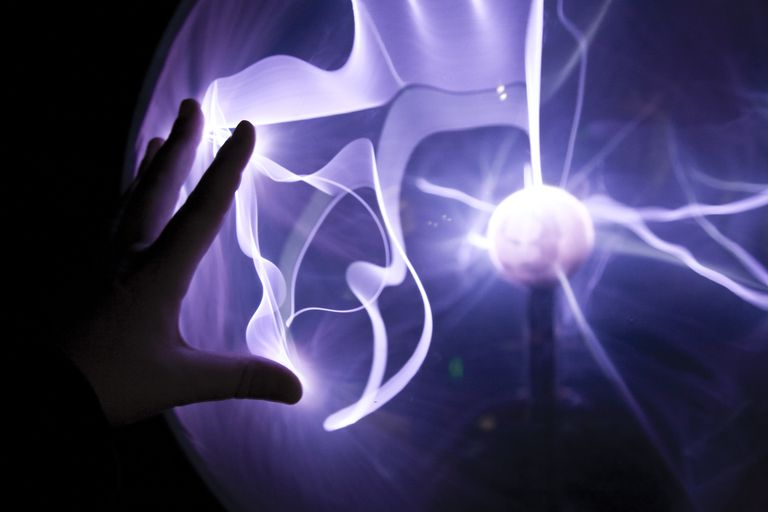 Closeup of a hand touching a plasma lamp.