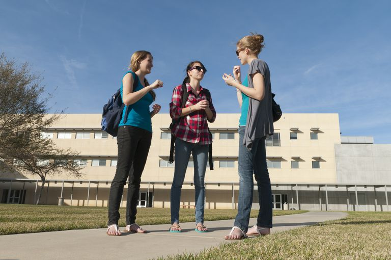 3 college-aged women having a conversation in ASL outside school