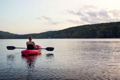 Woman Kayaking on a Serene Lake at Sunset