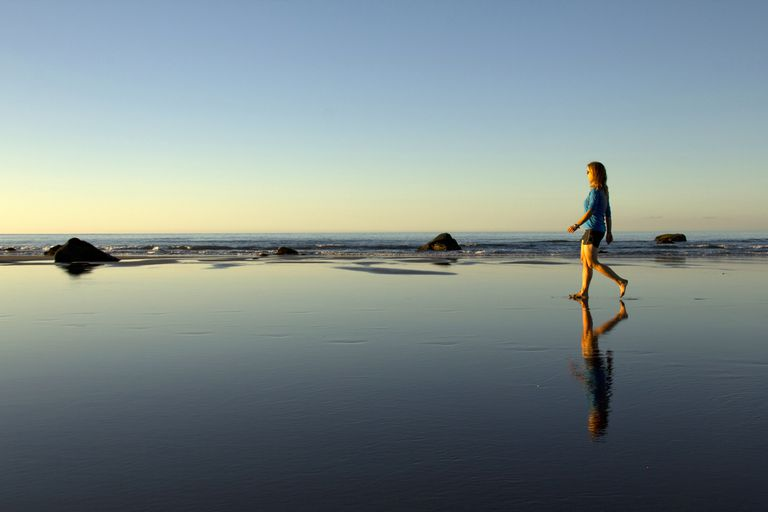Woman walking solo on beach
