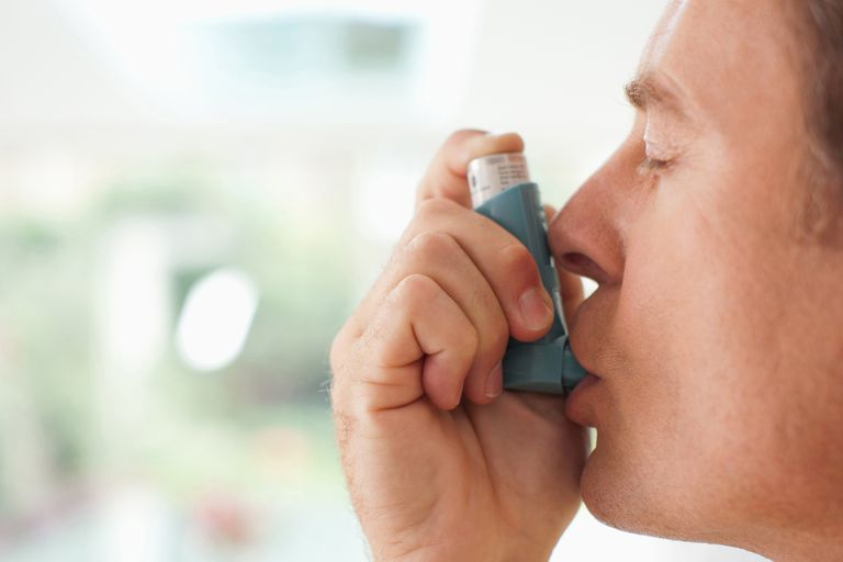 man with asthma using inhaler