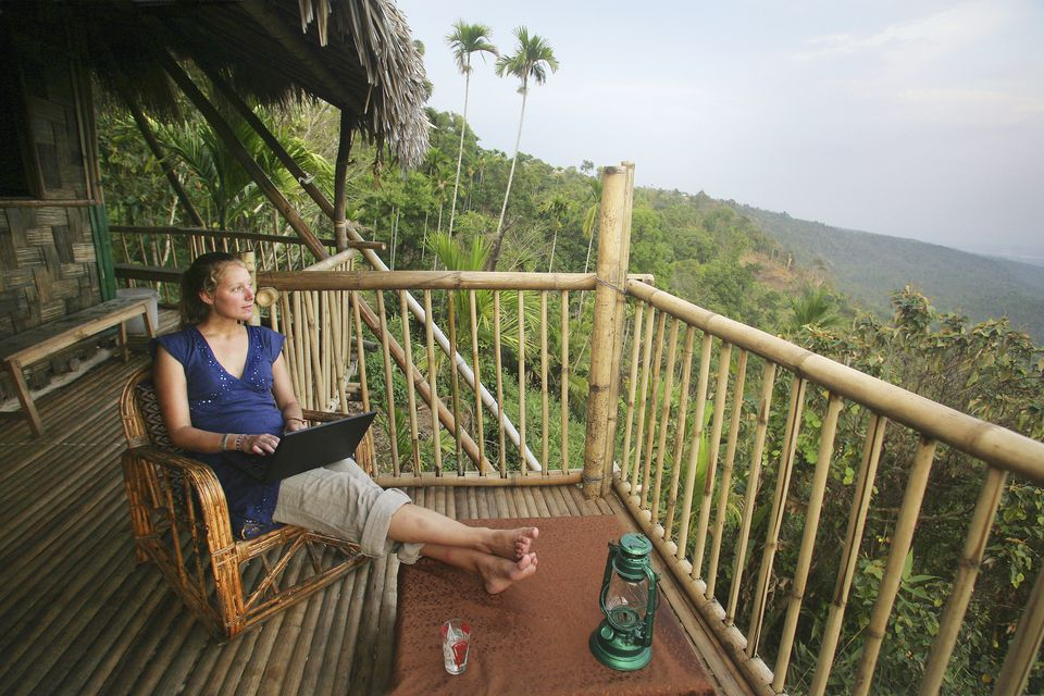 A Woman Using A Wireless Laptop Computer On The Balcony Of A Remote Bamboo Hut