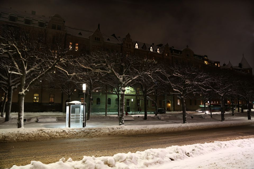 A telephone box in the snow at night beside a road in Stockholm in Sweden in winter