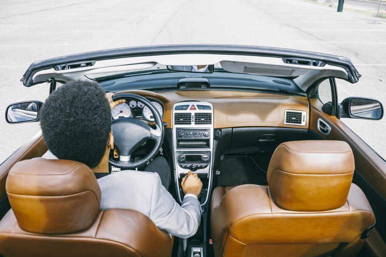 Man driving fancy convertible car