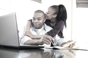 Dad paying bills online, teen daughter kissing Dad