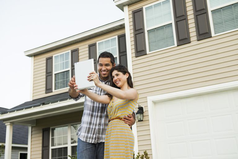 Couple Taking Self-Portrait in Front of their Home