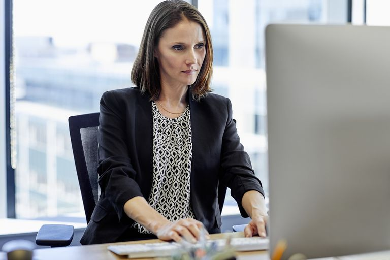 Confident businesswoman using computer on desk