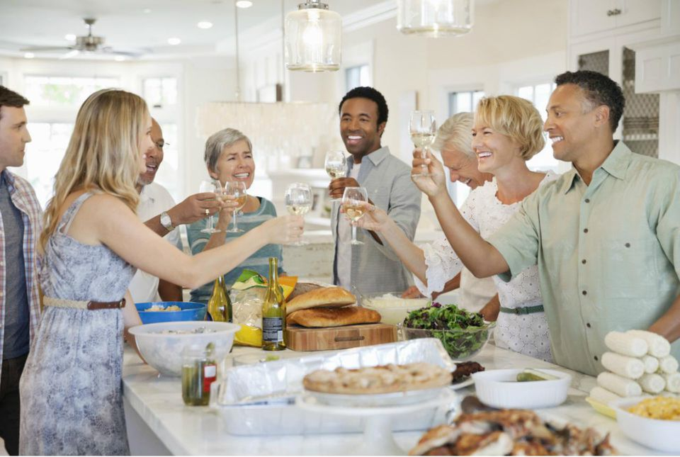 Happy multi-ethnic family and friends toasting with wine glasses at table