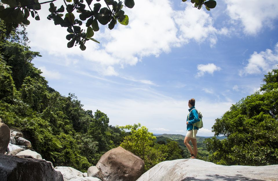 A woman stands on a rocky outcrop overlooking the jungle of Puerto Rico.