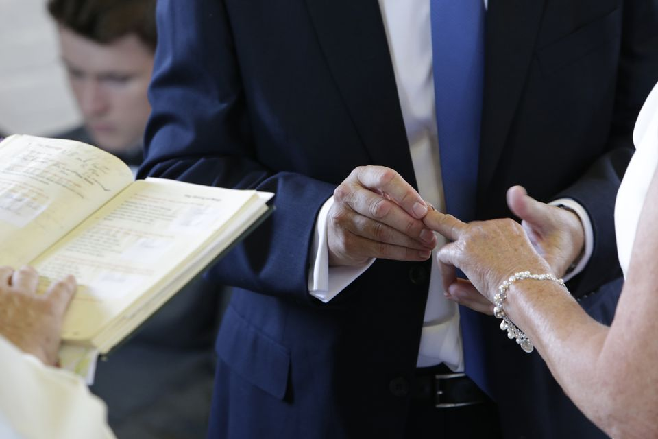 Wedding ring being put on brides finger