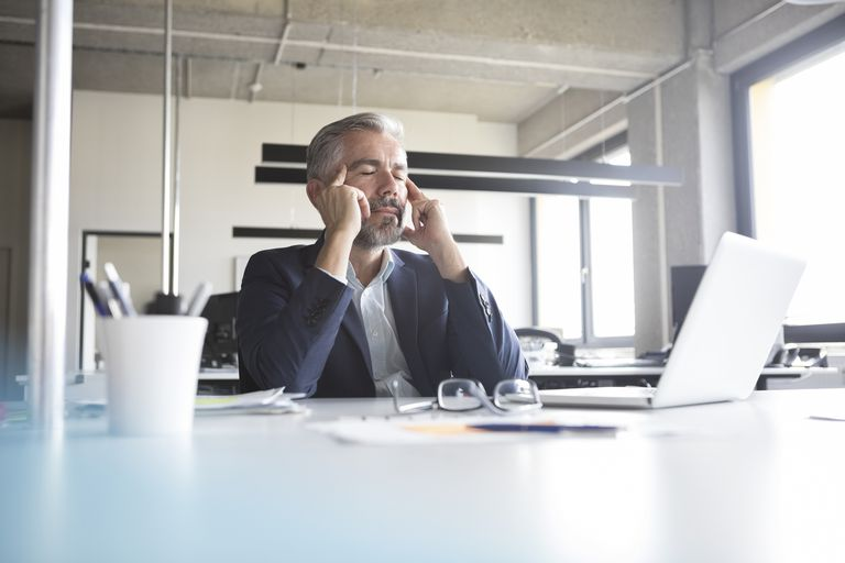 Businessman at desk in office with closed eyes