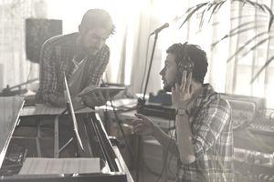 Two men at a piano using an iPad