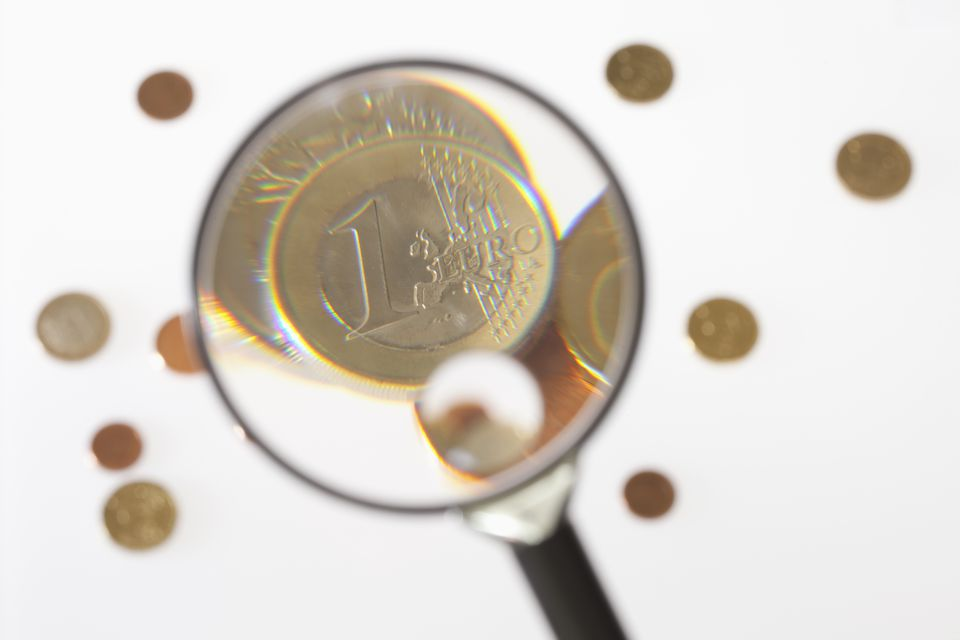 inspecting coins under a magnifying glass