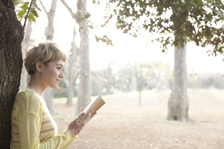 Fashionable Japanese woman reading book in park