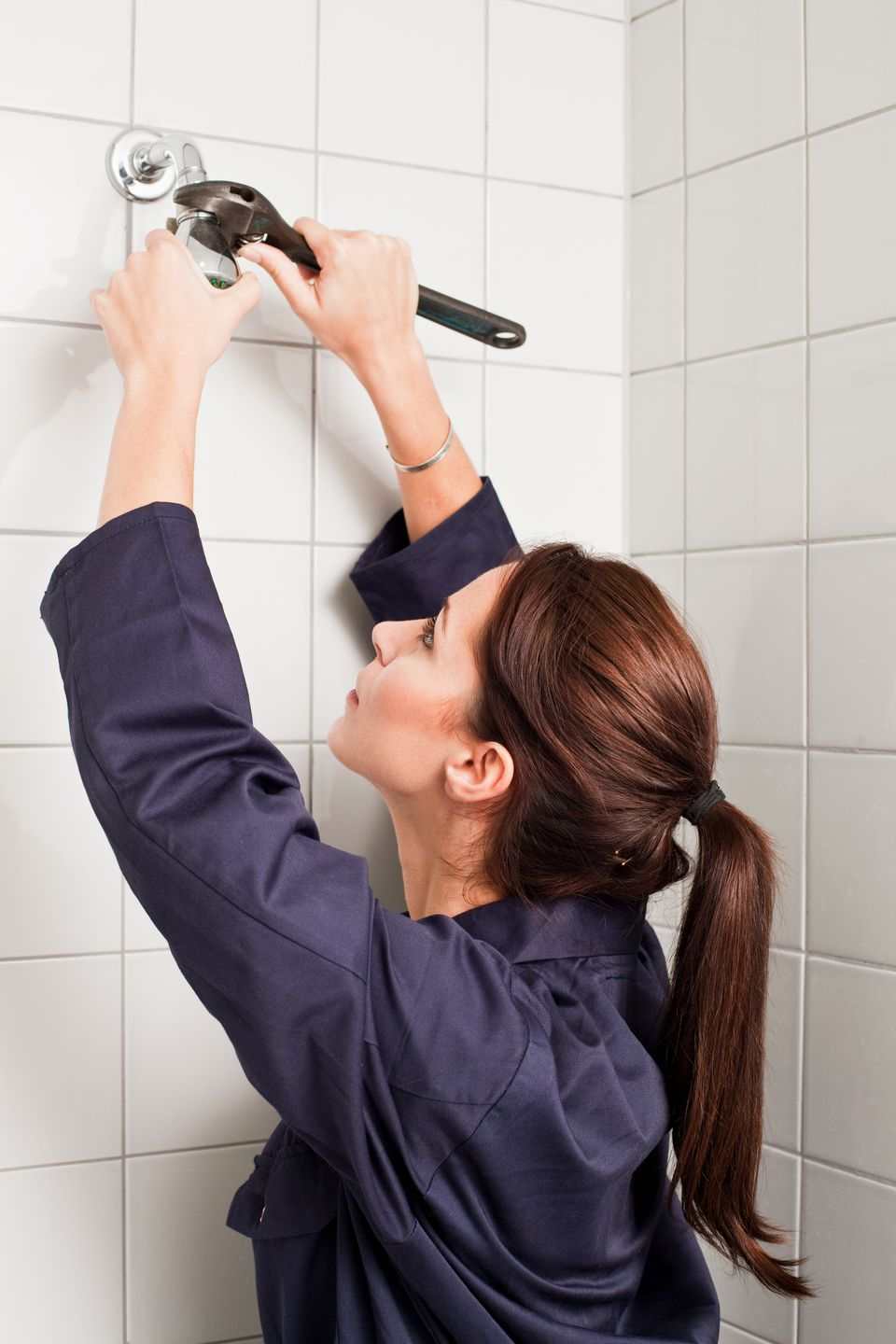 Female plumber fixing shower head