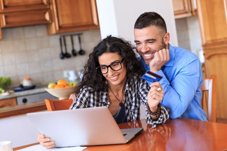 Couple using credit card and laptop at home, having fun.
