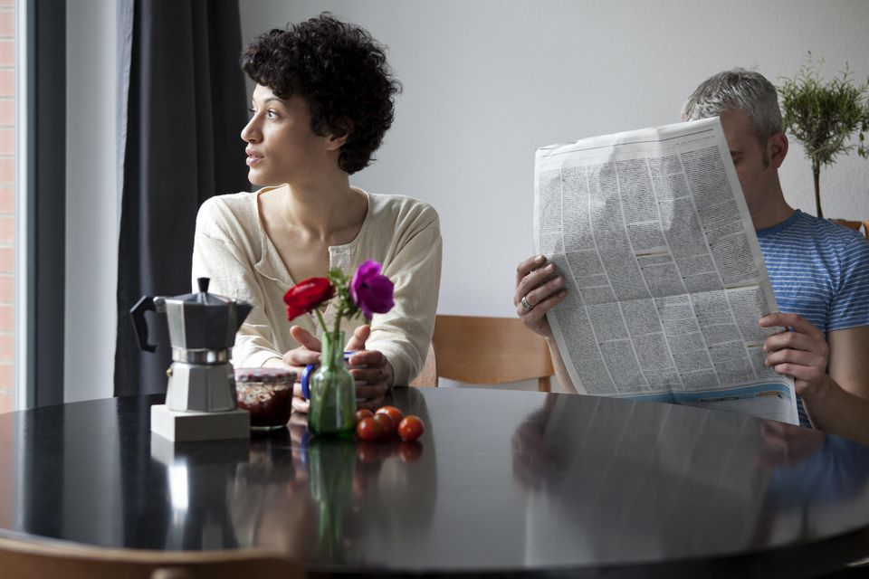 A serious woman looking out a window while her boyfriend hides behind a newspaper