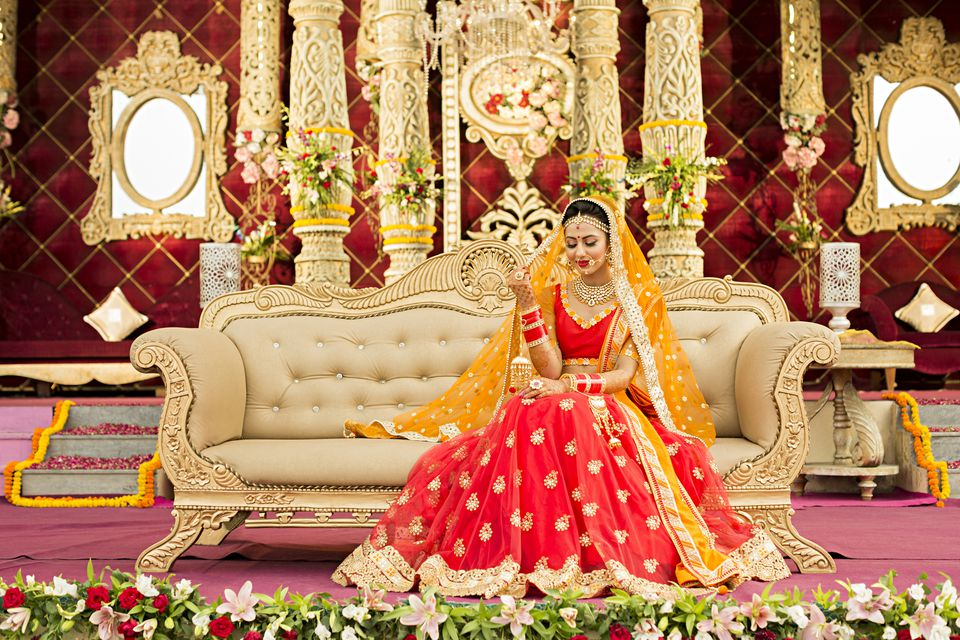 Bride wearing lehenga choli and sitting on sofa during wedding ceremony