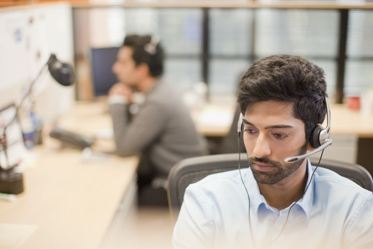 Indian businessman wearing headset at desk