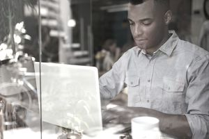 Man on computer in coffee shop