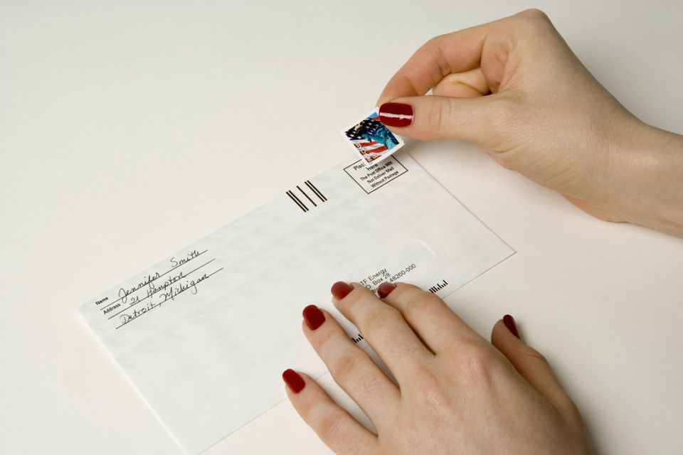 Woman fixing a stamp to a letter