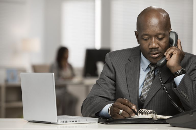 Black businessman using telephone to check references at his desk.