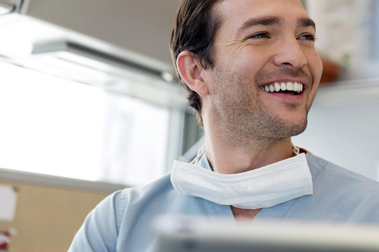 Happy male surgeon looking away in clinic