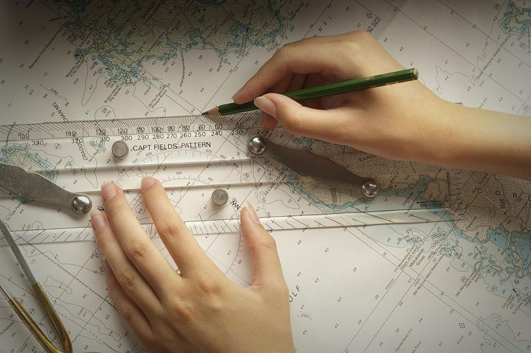 Woman's hands measuring on navigational chart.