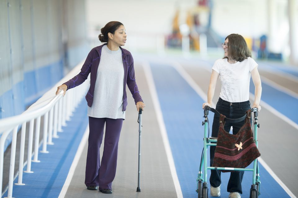 Disabled women using walker and cane on track