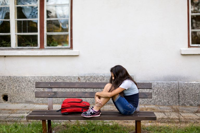young girl sitting on school bench