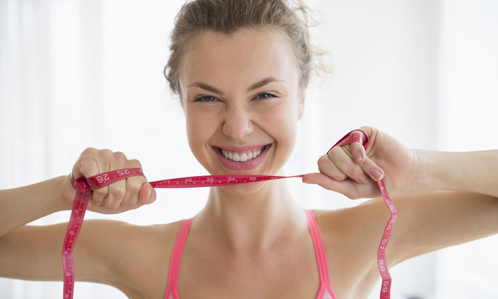 woman smiling with measuring tape