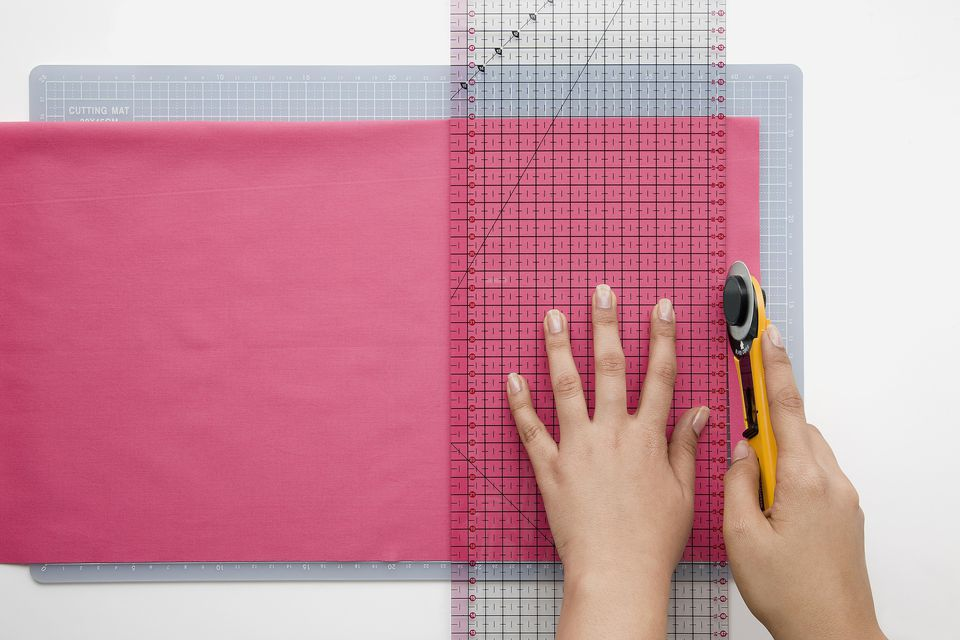 Woman cutting fabric using ruler and rotary cutter, close-up