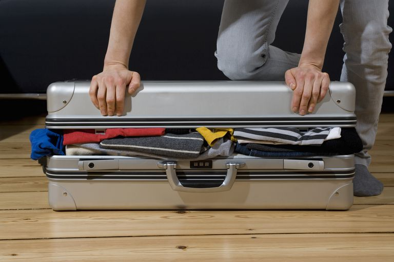 A person trying to close a stuffed suitcase