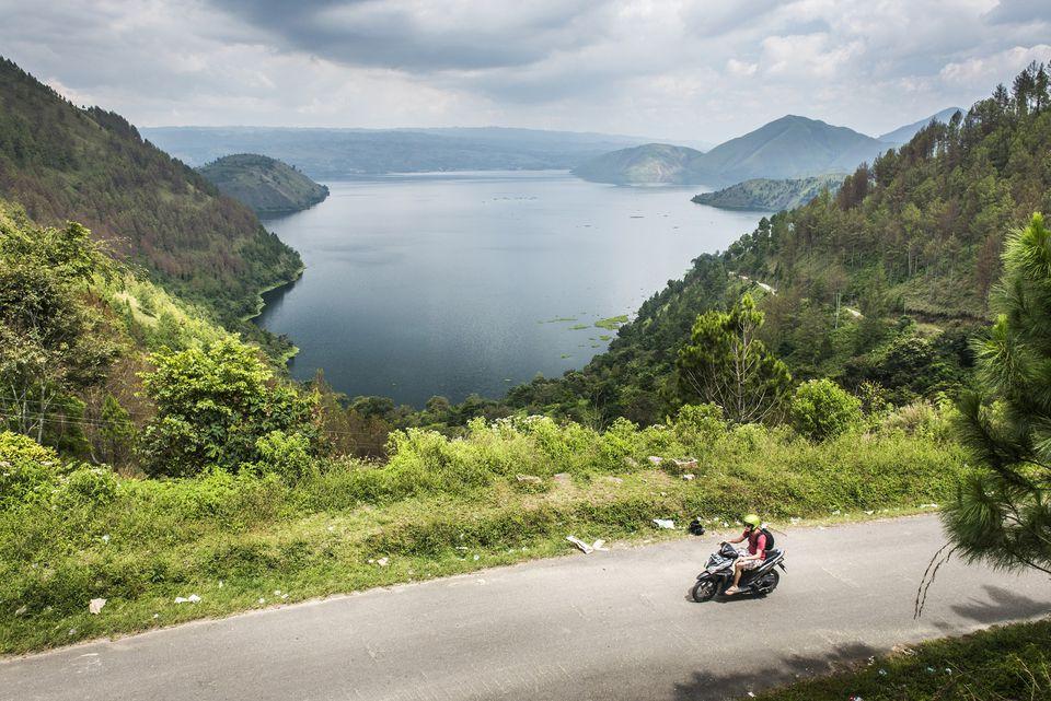 Tourist motorbiking along Samosir Island road, with Lake Toba view