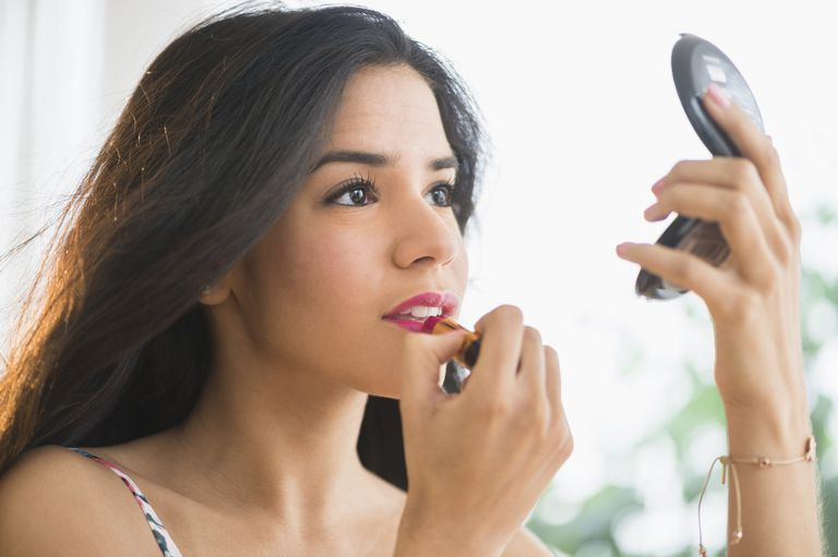 Latina woman applying makeup